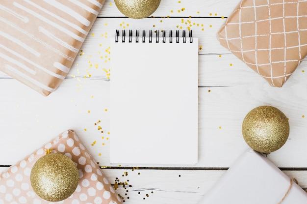 Caderno entre caixas de presente em envoltórios perto de bolas de natal