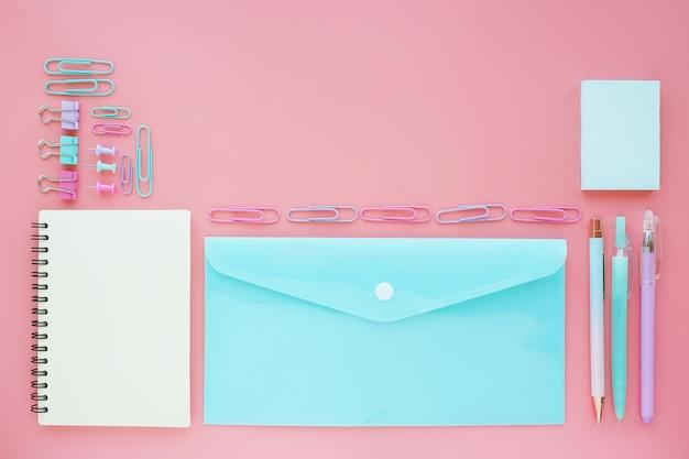 Caderno, envelope plástico, adesivos, canetas e clipes de papel de tons pastel em uma mesa rosa.
