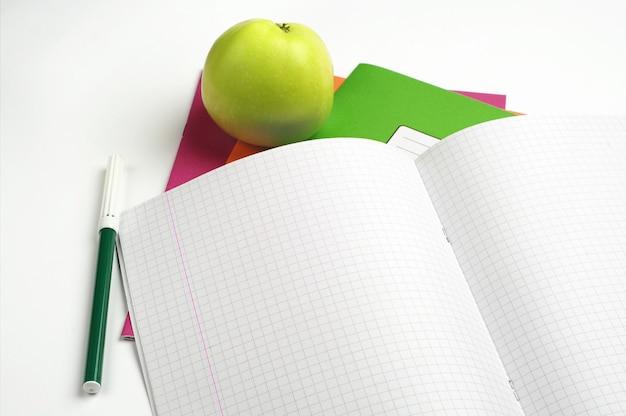 Caderno escolar aberto, canetas hidrográficas e maçã verde