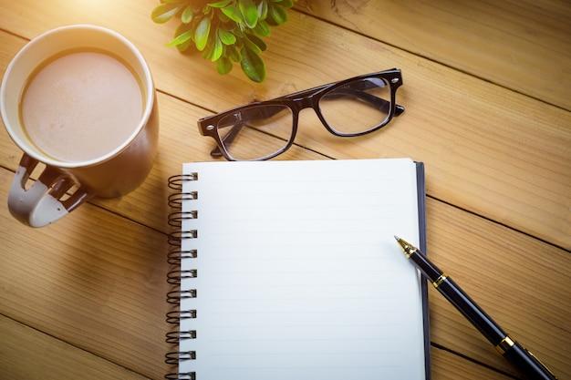 Caderno escolar com páginas em branco e com copos ao lado da xícara de café na mesa de madeira
