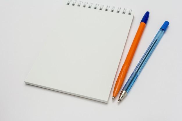 Caderno escolar vazio e canetas em uma superfície branca