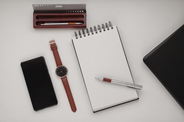 Caderno espiral branco aberto com uma folha em branco e muitos acessórios de escritório, um relógio de pulso, telefone celular, estojo para caneta e um laptop.