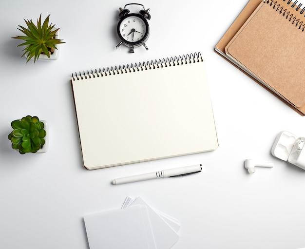Caderno espiral com folhas vazias, caneta e plantas verdes em uma panela, mesa branca