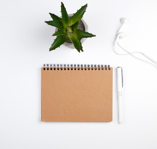 Caderno espiral com folhas vazias, caneta e plantas verdes