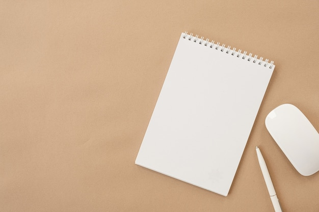 Caderno espiral de folha em branco, mouse, caneta na mesa bege pastel. camada plana, vista superior