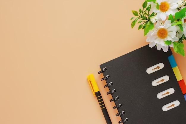 Caderno espiral e uma caneta com flores sobre fundo de cor bege para o conceito de espaço de trabalho