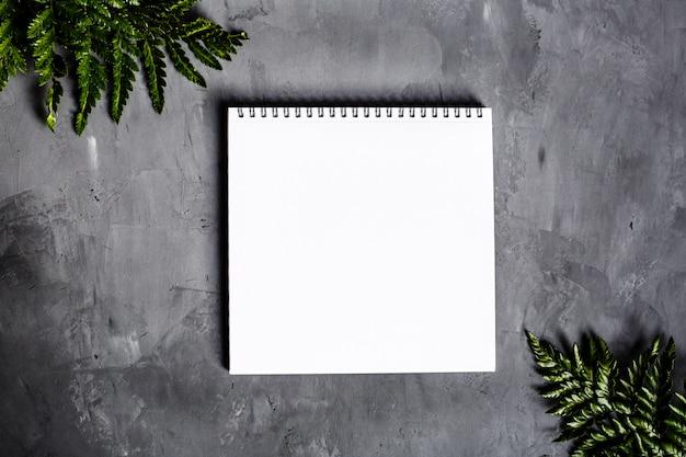 Caderno espiral em branco aberto, material escolar cinza em fundo de concreto