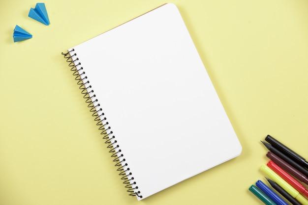 Caderno espiral em branco com caneta de ponta de feltro colorida em pano de fundo amarelo