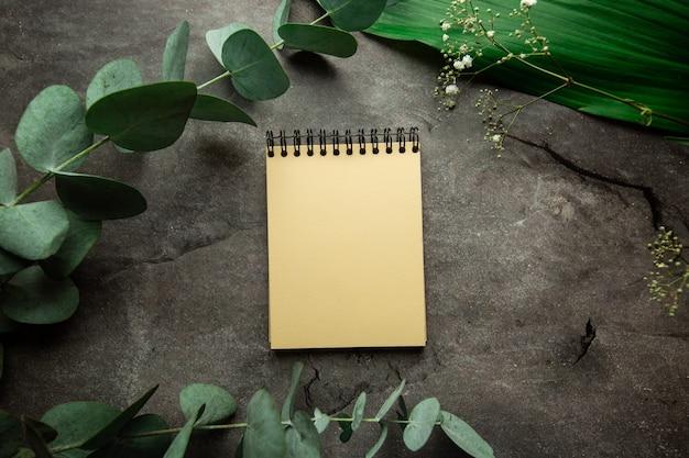 Caderno espiral em branco com lugar para texto em fundo cinza com folhas de plantas