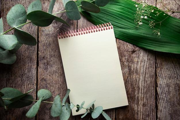 Caderno espiral em branco com lugar para texto em fundo de madeira com folhas de plantas e ramos de eucalipto vista de cima plana lay
