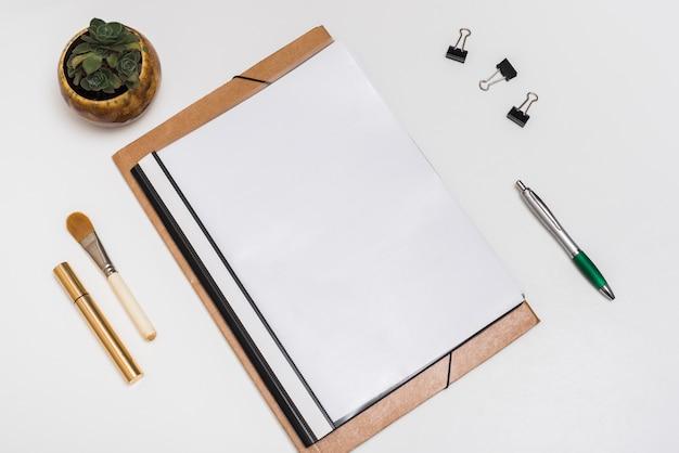 Caderno espiral em branco com pincel de maquiagem; rímel; clipes de papel e caneta com planta em vaso na mesa branca