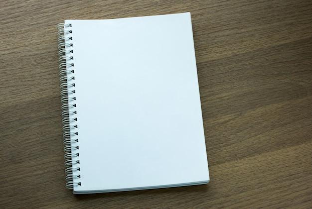 Caderno espiral em branco em fundo de madeira escura
