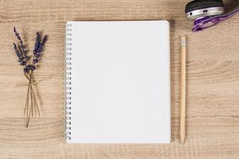 Caderno espiral em branco; lápis; galhos de fone de ouvido e lavanda em fundo de madeira
