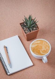 Caderno espiral em branco na mesa de madeira da mesa de escritório e uma xícara de café com leite