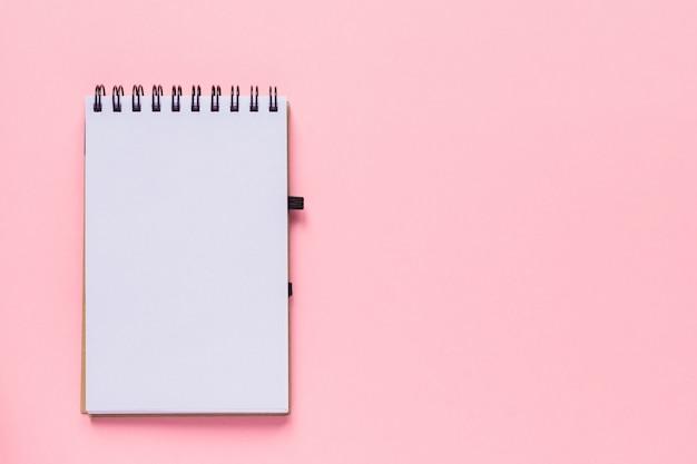 Caderno espiral limpo para anotações e mensagens sobre fundo rosa pastel. configuração mínima de negócios