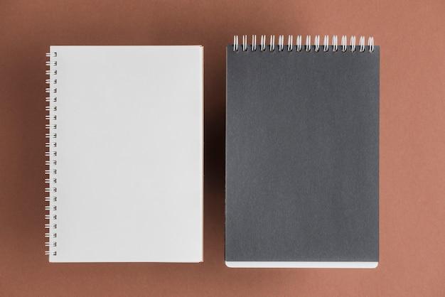 Caderno espiral preto e branco em fundo colorido