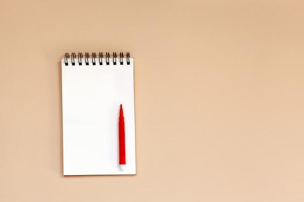 Caderno espiral vazio com a pena vermelha na tabela.