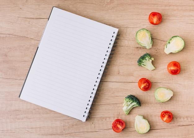 Caderno espiral vazio com couves-de-bruxelas divididas ao meio; tomates e brócolis na mesa de madeira