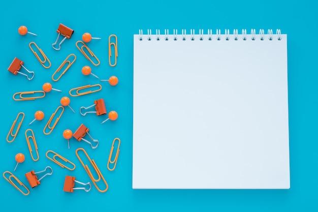 Caderno espiral vazio e clipes sobre fundo azul.