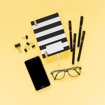 Caderno fechado com canetas de feltro; clipes de papel de bulldog; óculos e celular em fundo amarelo