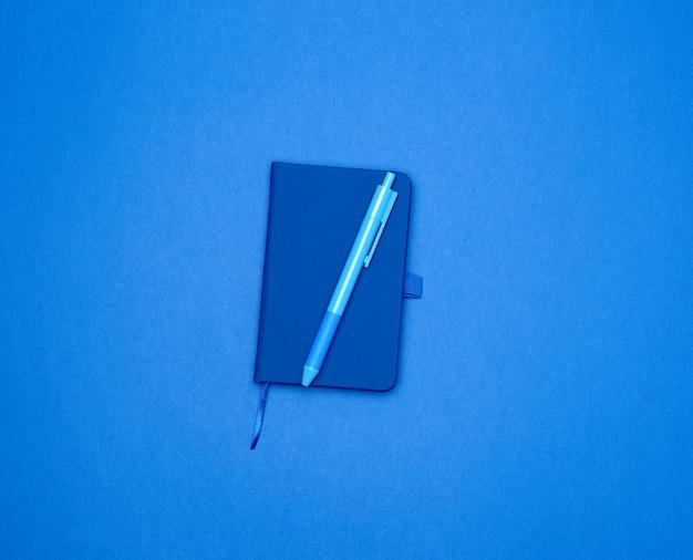 Caderno fechado e caneta azul em uma superfície colorida