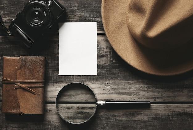 Caderno fechado em capa de couro, folha de papel branco, chapéu de feltro marrom, câmera e grande lupa isolada em mesa de madeira preta envelhecida