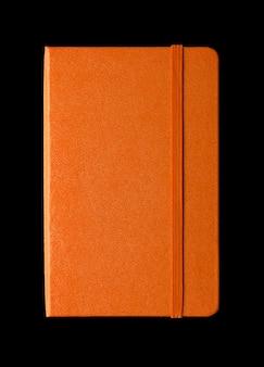 Caderno fechado laranja isolado no preto