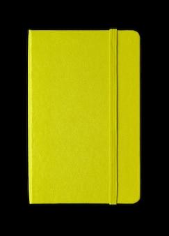 Caderno fechado verde limão isolado no preto