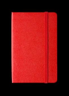 Caderno fechado vermelho isolado no preto