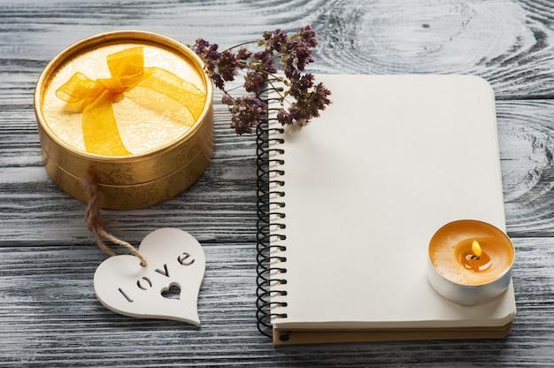 Caderno, flores secas, vela