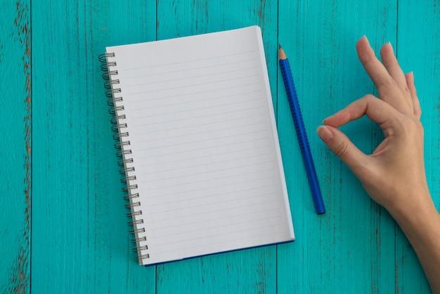 Caderno, lápis azul e mão feminina com gesto