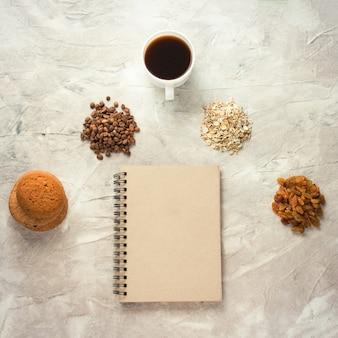 Caderno, lápis, biscoitos, aveia, café, passas e uma xícara de café. conceito de pequeno-almoço