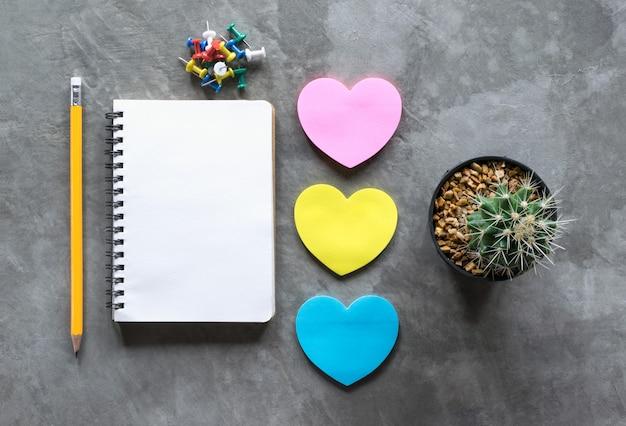 Caderno, lápis, coração de papel contra, cacto na opinião da placa do cimento de cima de.