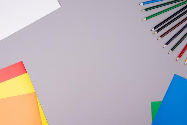 Caderno, lápis de cor e papel colorido