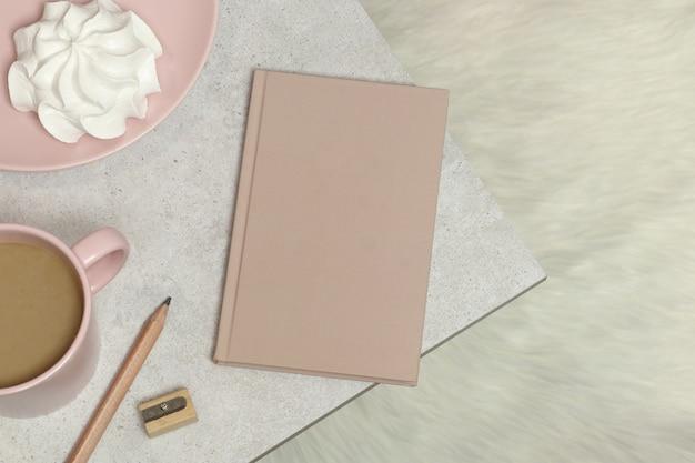 Caderno, lápis de madeira e apontador, xícara de café, marshmallow na mesa de granito