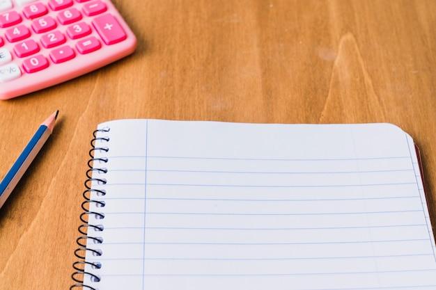 Caderno, lápis e calculadora na mesa de madeira