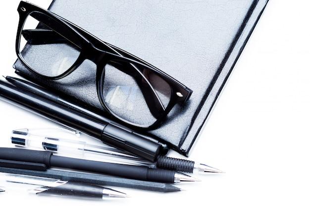 Caderno, lápis e óculos