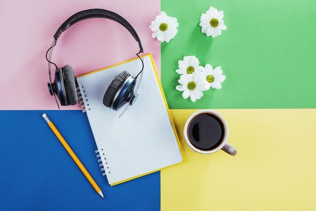 Caderno, lápis, fones de ouvido e café com sabor de flores brancas