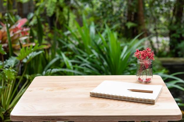 Caderno, lápis marrom e linda flor seca vermelha em vaso de vidro na mesa de madeira