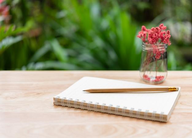 Caderno, lápis marrom e linda flor seca vermelha