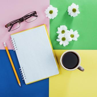 Caderno, lápis, óculos, café e flores brancas perfumadas.