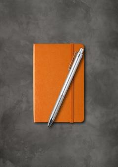 Caderno laranja fechado com uma caneta mockup isolada em fundo escuro de concreto