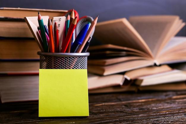 Caderno, livros abertos e suporte para canetas em uma mesa de madeira escura no fundo do quadro de giz