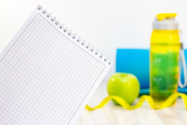 Caderno, maçã verde, fita métrica, garrafa de água e esteiras de esportes sobre um fundo claro de madeira. preparação para a temporada de verão e praia, perda de peso e conceito esportivo