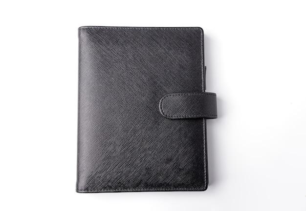 Caderno magnético preto isolado em um fundo branco, a superfície da capa do caderno é áspera.