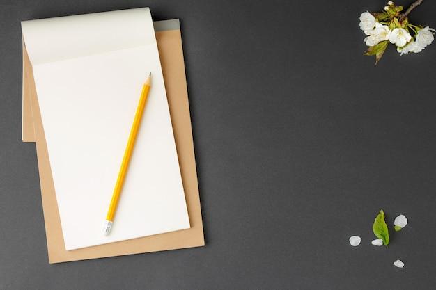 Caderno marrom com caneta de lápis amarela