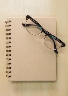 Caderno marrom com óculos em fundo de madeira