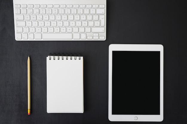 Caderno, mesa e teclado na mesa escura