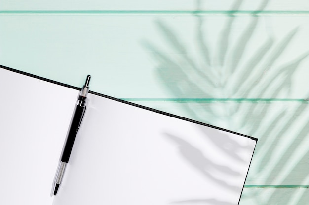 Caderno minimalista com caneta e folhas de sombra