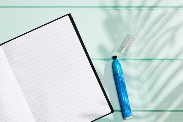 Caderno minimalista com marca-texto e sombra de folhas